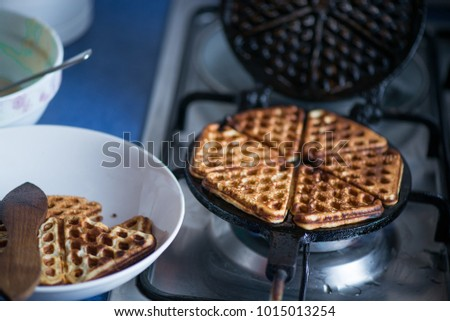 Just cooked, delicious, tasty, hot yogurt pancakes on waffle iron on fire stove in kitchen. Dinner is ready. Sweet golden brown waffles ready to be eaten #1015013254