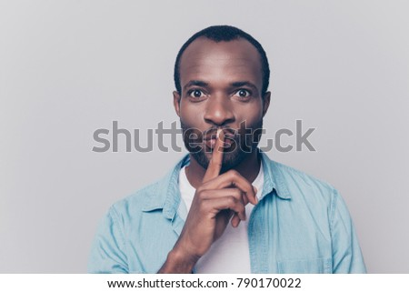 Just don't speak! Close up portrait of handsome cheerful mysterious silent man making hush gesture, isolated on gray background