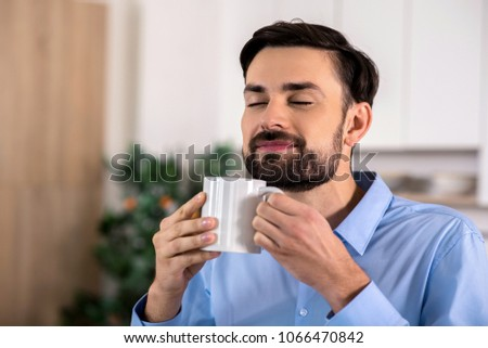 Just enjoy. Cheerful handsome businessman smelling his coffee in the kitchen #1066470842