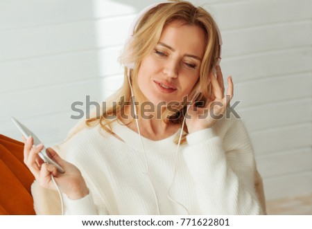 Just enjoy it. Close up of delighted nice woman listening to music while enjoying her rest at home #771622801