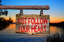 Just follow your heart motivational phrase sign on old wood with blurred background