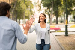 Just Friends. Girl Waving Hello Meeting Guy Walking In Park Outside. Selective Focus