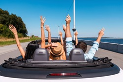 Just fun and road ahead. Rear view of young happy people enjoying road trip in their convertible and raising their arms up