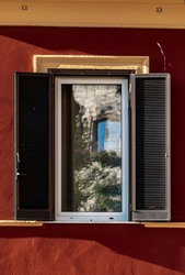 Just in front of Colosseum and the Palatino hill (the residence of Roman Emperors) you find some of the most expensive apartments in Rome. The top level of Colosseum is reflected in the window glass.