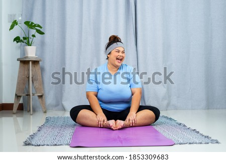 Just keep calm and do sport! Peace rest relaxation vitality concept. Cheerful curvy fatty concentrated oversize with flabby belly woman is doing yoga on purple mat on the floor at home. Photo stock ©