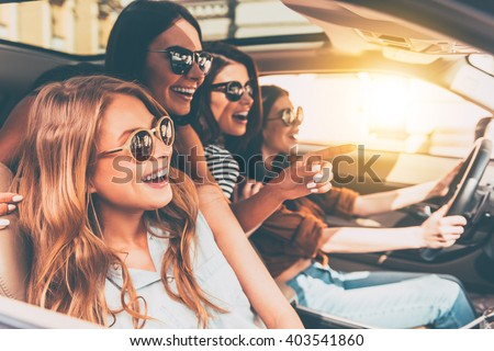 Just keep driving! Side view of four beautiful young cheerful women looking away with smile while sitting in car  #403541860