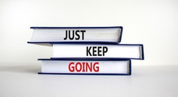Just keep going symbol. Books with words 'Just keep going'. Beautiful white background. Business, just keep going concept, copy space.
