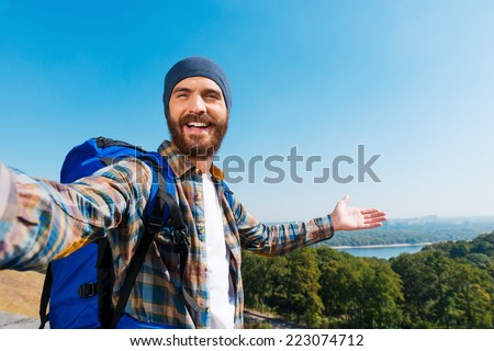 Just look! I am here! Handsome young man carrying backpack and taking a picture of himself and pointing to the view
