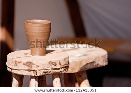 Just made wet clay cup drying on a potter table - stock photo