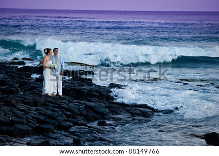 Just Married. Beautiful young couple on a rocky beach on their wedding day.  The waves of the ocean are crashing in the background.