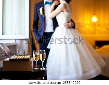 Just married couple, champagne and box of chocolates near a window. Groom embraces bride. Focus on champagne in front of couple