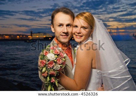 Just married couple near the river at sunset time