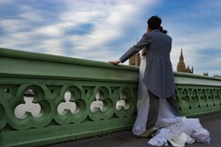 Just married couple standing at Westminster bridge in London, England