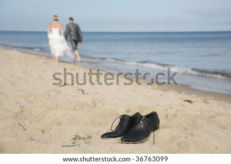 Just married couple walking on the seashore with focus on the man's shoes