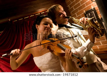 Just married. Happy couple playing music at club