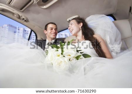Just married joyful young couple inside limo