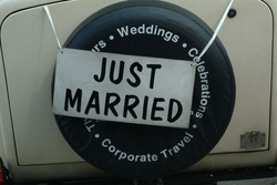 Just married sign hanging from the back of a car. Tied on with ribbon over spare wheel at a wedding.