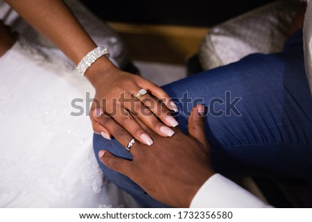 Just married young African couple's hands, holding together, new golden rings with diamonds, long fingers, wedding manicure, shiny wedding bracelet, white dress, blue groom's suit, white shirt Сток-фото ©