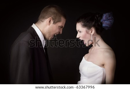 Just married young caucasian couple arguing and shouting at each other, on black background isolated