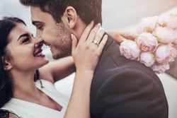 Just married Young romantic couple is hugging and kissing near private plane. Attractive woman in wedding dress and handsome man in suit are celebrating wedding day in airport near airplane Honeymoon.