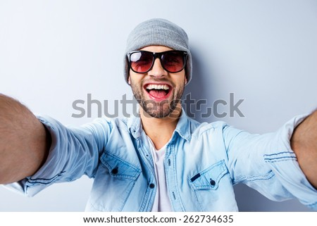 Just me and no one else. Top view of handsome young man in hat and sunglasses making selfie and smiling while standing against grey background #262734635