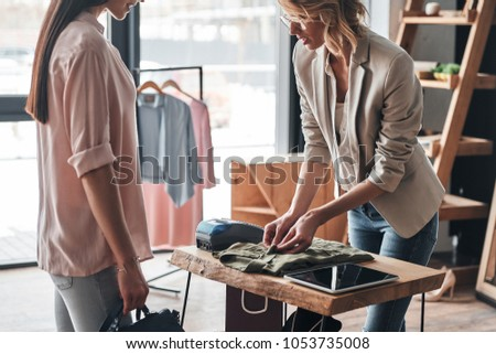 Just one moment. Beautiful young woman folding a shirt for her customer while working in the fashion boutique                 #1053735008