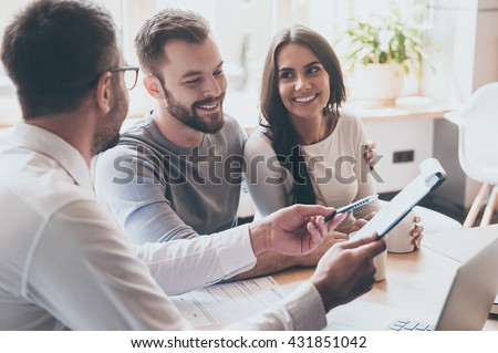 Just put your signature here! Confident young man in shirt and tie holding some document and pointing it while sitting together with cheerful young couple at the desk in office