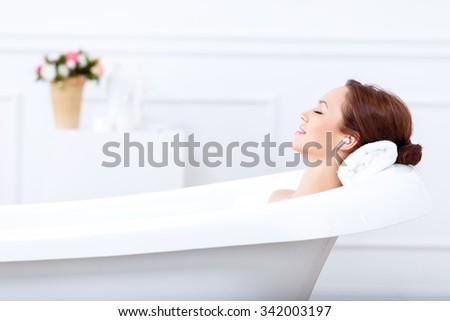 Just relax. Content beautiful young woman listening to music and closing her eyes while taking a bath
