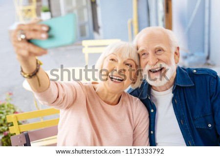 Just smile. Enthusiastic senior couple sitting at cafe and using phone #1171333792