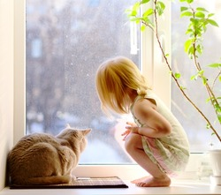 Just stay at home. Cat and girl looking out of the window. Self quarantine concept. Coronavirus pandemic social isolation.