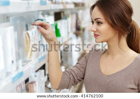 Just what I need. Horizontal portrait of a young cheerful woman customer choosing products in an aisle at the drugstore.