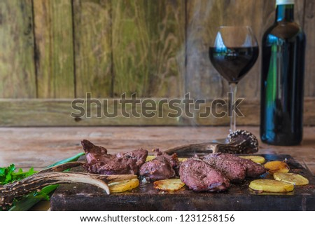 Juste cooked hunter's meal smoking roasted deer meat with potatoes, bottle and glass of red wine on the rustic wooden background with copy space