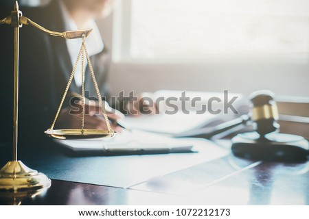 Justice and Law concept. Legal counsel presents to the client a signed contract with gavel and legal law or legal having team meeting at law firm in background #1072212173