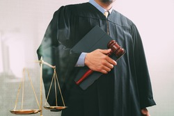 justice and law concept.Male judge in a courtroom holding the gavel and balance scale and digital tablet computer hand wood hammer.