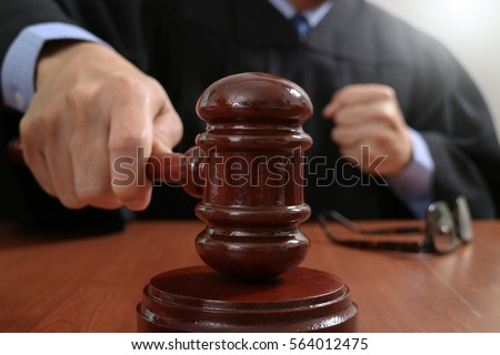 justice and law concept.Male judge in a courtroom striking the gavel,working with digital tablet computer docking keyboard on wood table Foto d'archivio ©