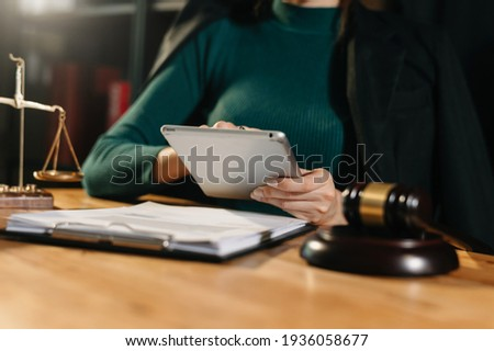 justice and law concept.Male judge in a courtroom  the gavel, working with smart phone and laptop and digital tablet computer on wood table in morning light  Photo stock ©