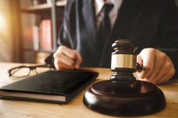 justice and law concept.Male judge in a courtroom with the gavel,working with,digital tablet computer docking keyboard,eyeglasses,on wood table in morning light