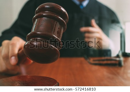 justice and law concept.Male judge in a courtroom with the gavel,working with smart phone,digital tablet computer docking keyboard,eyeglasses,on wood table Foto d'archivio ©