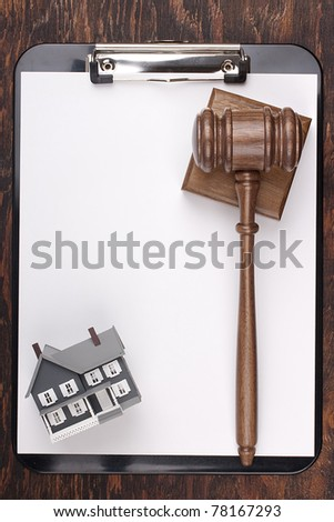 Justice gavel and house model on a clipboard. Add your text to the paper.