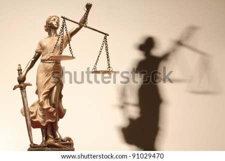 Justice (greek:themis,latin:justitia) blindfolded with scales, sword and her shadow on the background. Sepia toned image