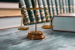 Justice Scales and books on wooden table
