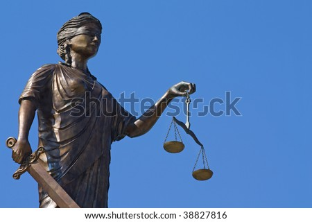 Justice statue with scales and sword on the blue sky background