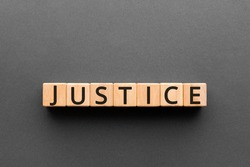 Justice - word from wooden blocks with letters, a judge or magistrate justice concept, black background