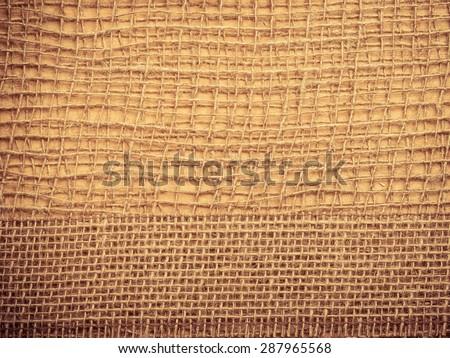 Jute bagging ribbon on brown mesh material, natural burlap ecology background