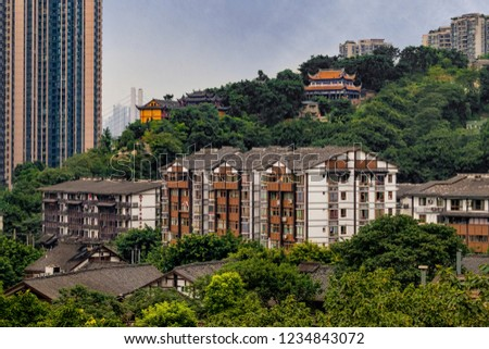Juxtaposition of Old Buildings and Historic Temples with Modern Concrete Apartment High Rise Blocks in Chinese City. Apartments surrounded by Forest Trees on Hillside (Chongqing, China).