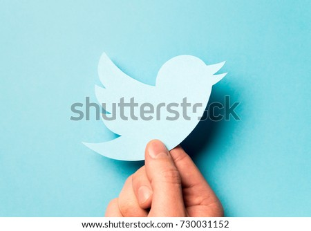 JYVASKYLA, FINLAND - OCTOBER 7, 2017: Hand holding printed cardboard paper Twitter logo in hand against blue background. Twitter is a social media network founded in 2006. Illustrative editorial.
