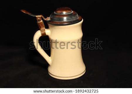 Kávé kiöntésre szolgáló kiöntő. A fedő része fémből készült a test része pedig kiégetet agyagból amit egy mázzal vontak be. Fekete háttérrel. Stock fotó ©