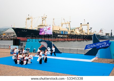 KAGOSHIMA CITY, JAPAN - APRIL 27:    A dance group performs at a Japanese Whaling Festival with whaling factory ship Nisshin Maru in the background April 27, 2008 in Kagoshima City, Japan.