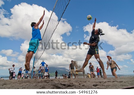 KAGOSHIMA CITY, JAPAN - JULY 1: A male volleyball player jumps to spike at the Iso Beach beach volleyball competition July 1, 2007 in Kagoshima City. Active volcano Sakurajima is in the background.
