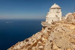 Kalamiotissa monastery on high rocky mountain on Greek island Anafi in Cyclades, Greece